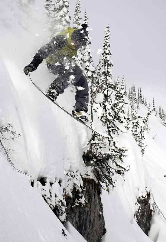 Derek Root grabs his tail as he drops over a cliff at Island Lake Lodge, Fernie, BC.