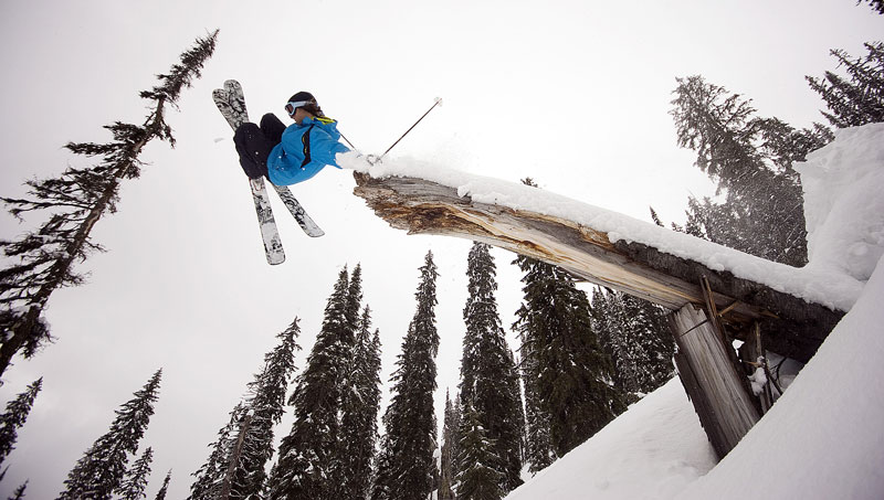 Jordan Sinnott grabs some snowy lumber as he airs past a tipped over tree stump.