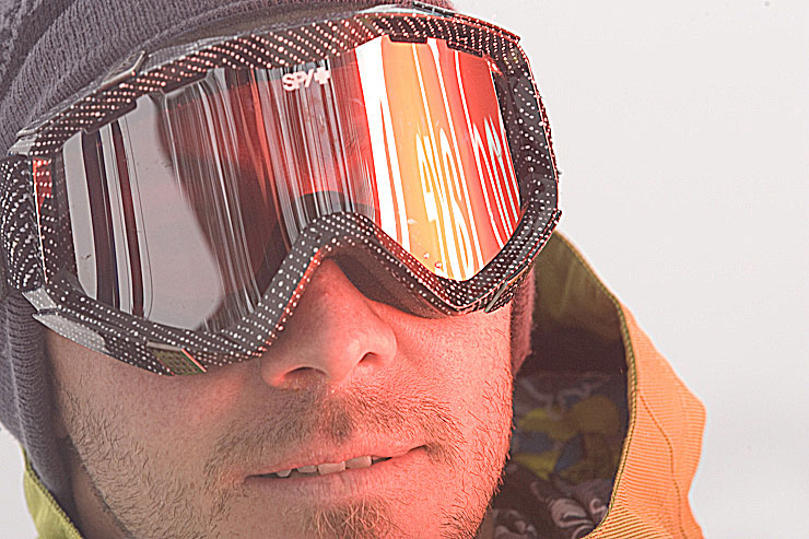 The logo on the back of the Cat is reflected in the goggles of Derek Root at Island Lake Lodge, Fernie, BC.