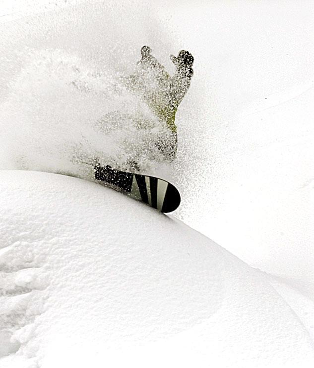 Derek Root power slashes a powder pillow at Island Lake Lodge, Fernie, BC.