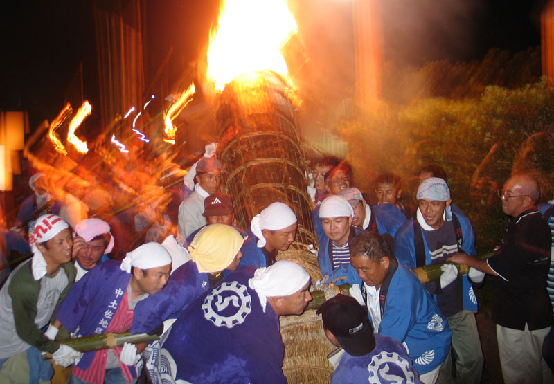 A burning tree is hoisted at the beginning of a festival in Nakatosa, Shikoku. The tree was paraded into the centre of town where teams battled with huge drums during the all night long affair.