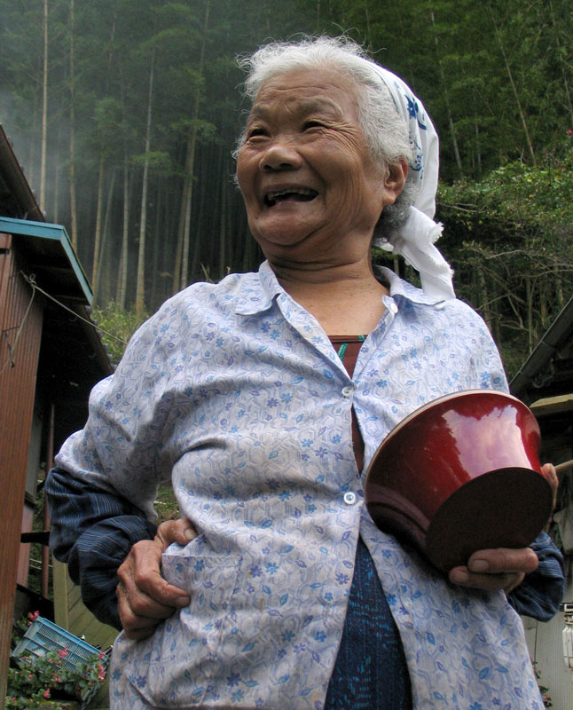 A woman shares a laugh while offering some candy in the mountains on the island of Kyushu, Japan.