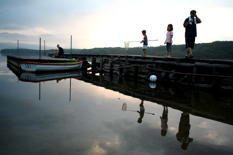 A young boy scans the still water with his fishing net as his sister and dad stand near-by and a young couple sit at the end of the dock on a peaceful night.