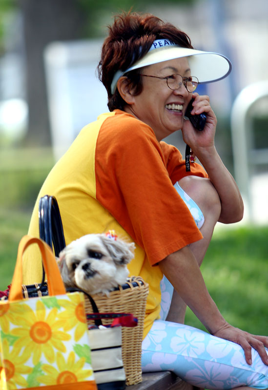 A woman chats on the phone while her dog sits patiently in a hand basket in the city of Hakodate, on the northern island of Hokkaido in Japan.