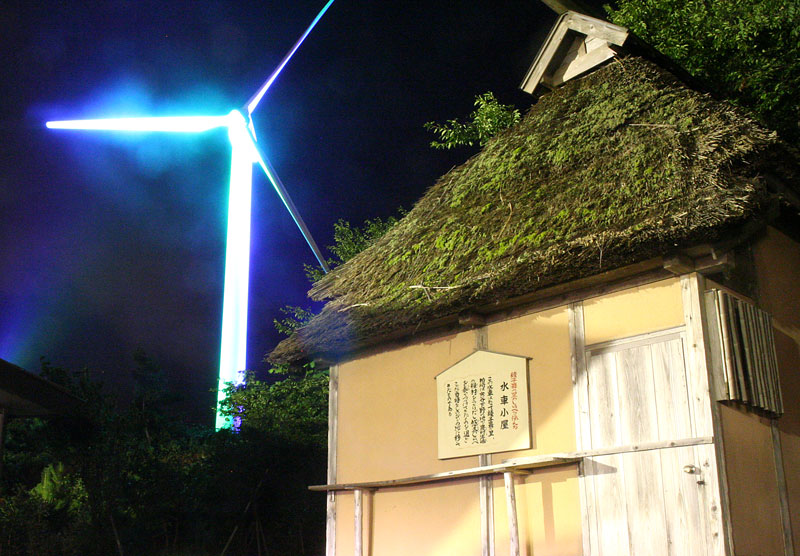 A grass roofed hut is juxtaposed with a modern wind generator that is illuminated with a blue spotlight.