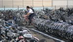 A man rides his bike through the Nagano Station bike parking during rush hour in Nagano, Honshu.