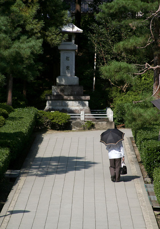 A person walks under the shade of an umbrella in the grounds of 1400 year old Zenkoji Temple, Nagano, Honshu.