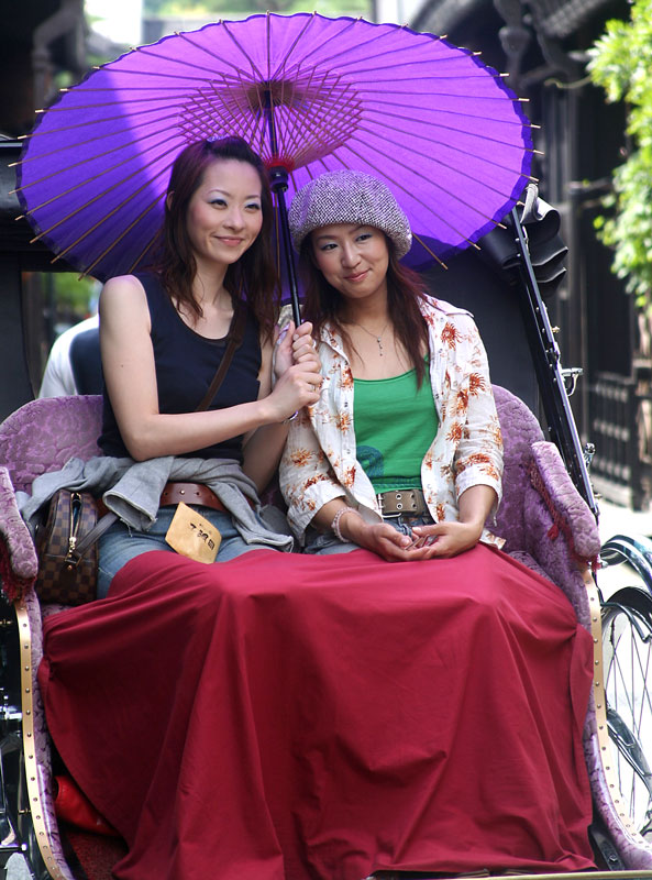 Two girls take some shade and pose for a photograph while on a rickshaw tour in Takayama, Honshu, Japan.