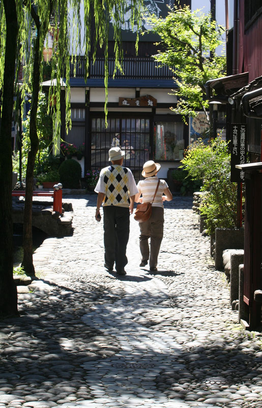 A couple tours the side-streets of Gujo-Hachiman, in Honshu.