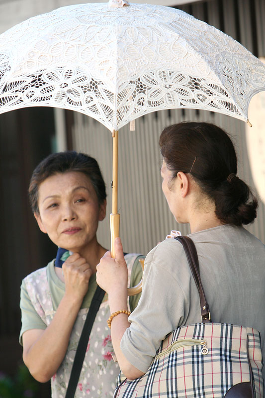 Two women have a street-side chat inGujo-Hachiman. Umbrellas are a very popular item in Japan, commonly used to keep the sun off and translate into a fashion accesory.