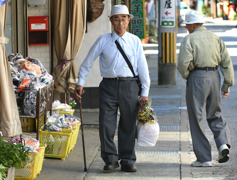 Two men pass on the street while out running errands in Gujo-Hachiman, Japan.