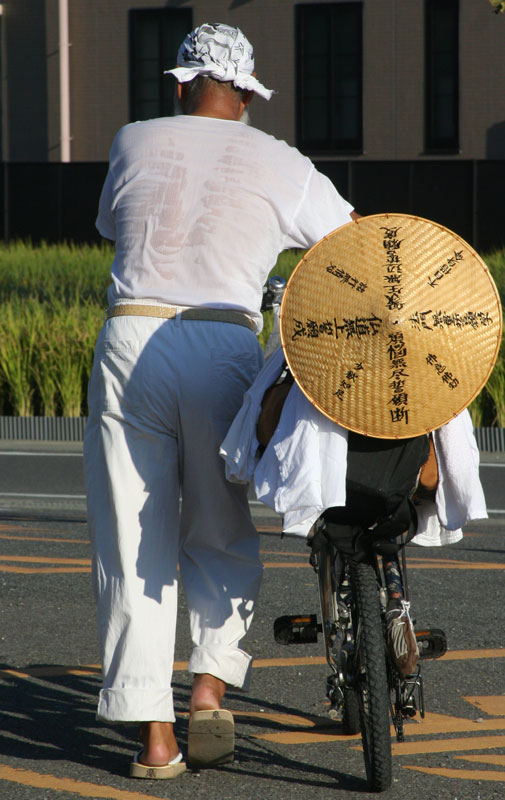 The shirt of a pilgrim is already soaked as he heads out for another day on the road on the 88 temple pilgrimage around the island of Shikoku.