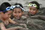 Three boys have fun on the beach after being burried in the sand on Japan's island of Shikoku.