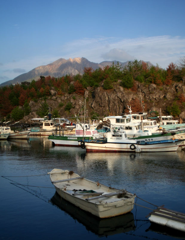 Fishing boats lie in wait beneath the worlds most active volcano, Sakurajima, near Kagoshima, Kyushu.