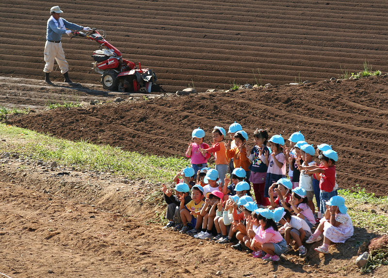 A group of school children pose for a photo while on a field trip to a farmers field on Nagashima Island, Kyushu.