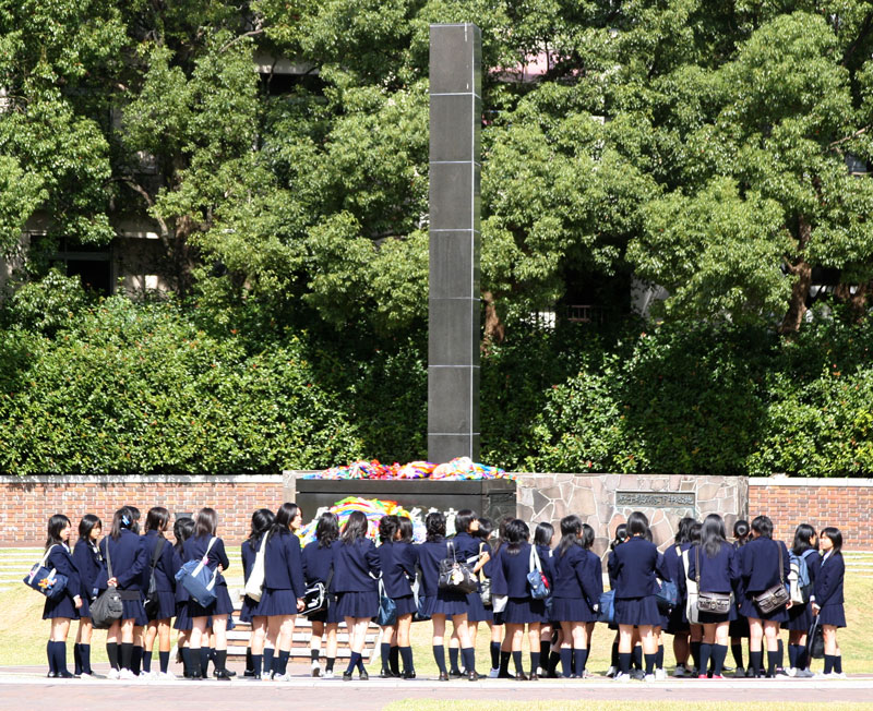 Japanese school girls visit the hypocentre marking ground zero where the atomic bomb hit Nagasaki on August 9, 1945. Nagasaki, Kyushu.