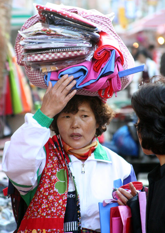 A woman balances her goods as she tries to make a sale in a street market in Haeundae-gu, Busan, South Korea.