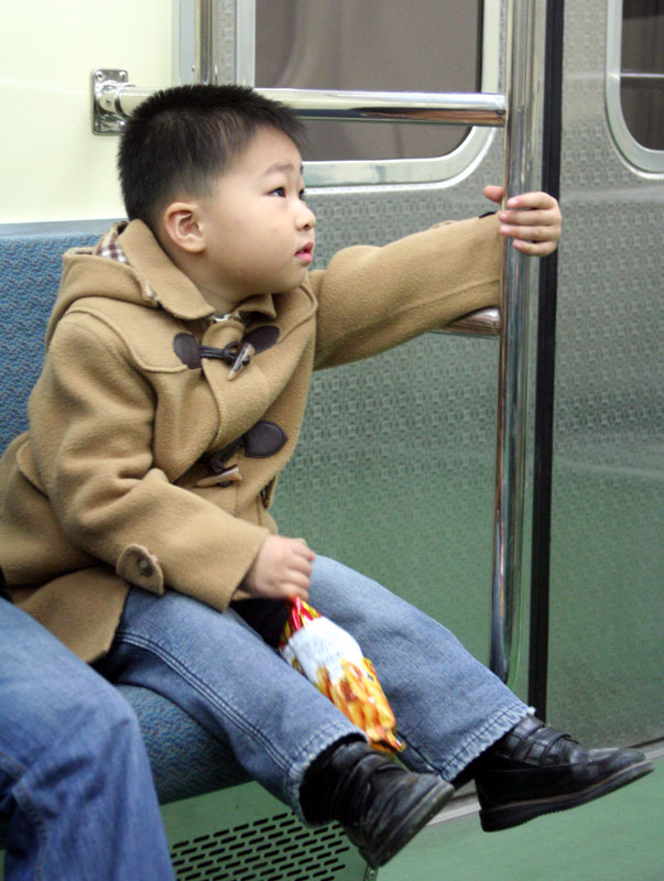 A boy is dressed to impress as he rides the train in Busan, South Korea.