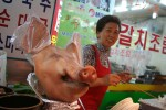 A pig head is on display as a vendor looks over at a market in Seoul.