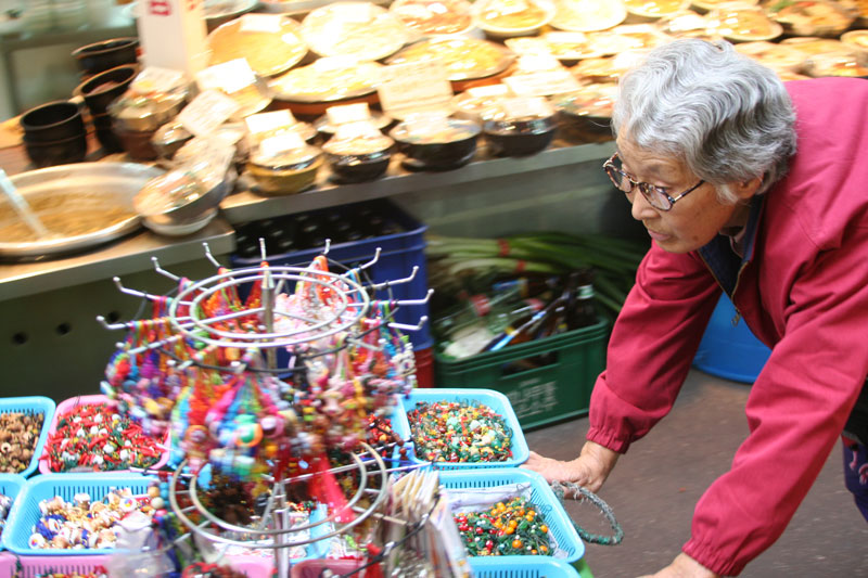 A woman pushes her cart of beads through a market in Seoul, South Korea.
