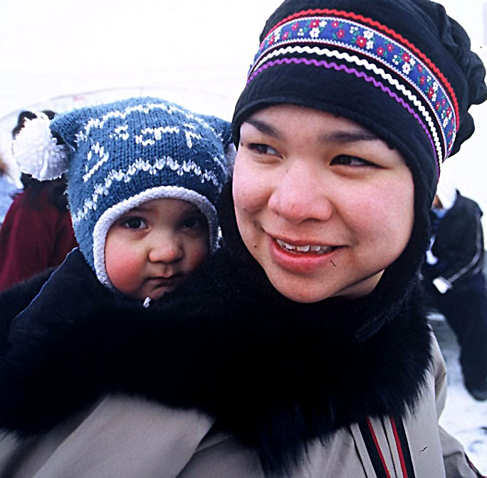 An Inuk woman keeps her baby warm in a traditional kamik while enjoying the sights and sounds of Caribou Carnival in Yellowknife, NWT.