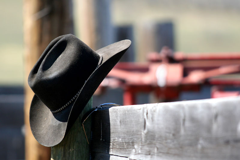 A cowboy hat and shades sit on a fence rail.