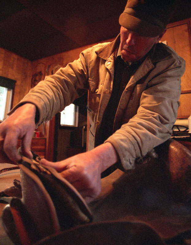 A cowboys work is never done. Repair of a favourite saddle commences after the other day's chores are done.