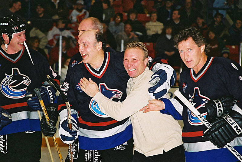 Tiger Williams gives a helping hand to teammate Edie Mio after the Vancouver Canucks Alumni Team won the Three-on-Three Charity HockeyTournament in Calgary.