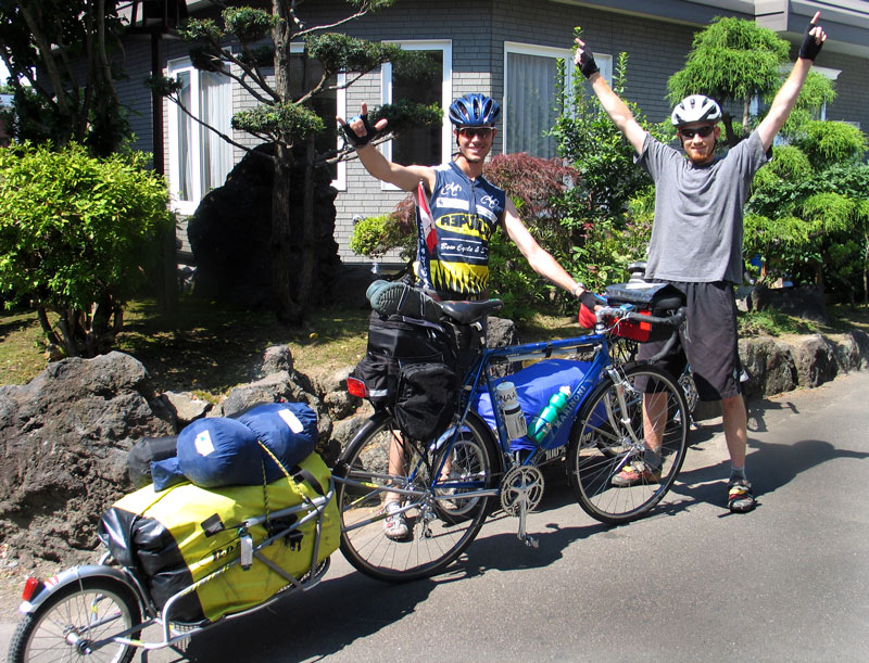 Ready to Ride! Aaron on the left and Reid on the right at kilometer zero. Ride day one began in Sapporo, Hokkaido with an afternoon start and a few gear pitstops on the way out of the city. Photo taken by friend.