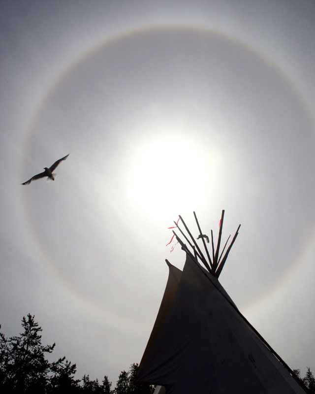A bird soars above a tepee as a sundog graces the northern sky while Aboriginal Day festivities take place in Yellowknife, NWT, Canada.