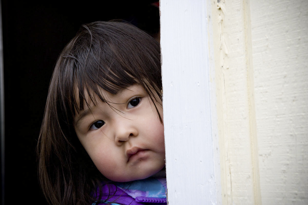 A young girl from Chignik peers out the door of the Donut Hole bakery, the closest thing the town has to a restaurant.
