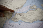 Cadet Chris Buckley plots a course across Ikatan Bay from Cold Bay to False Pass, from the bridge of the M/V Tustumena.