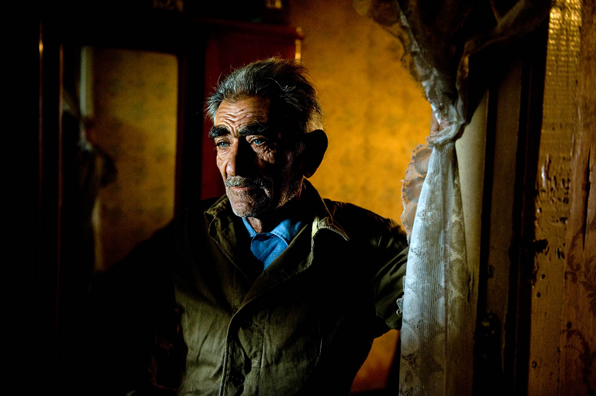 Norayr Sargsyan inside his family's dilapidated apartment, in a crumbling Soviet-era apartment building.  © Habitat for Humanity International/Ezra Millstein
