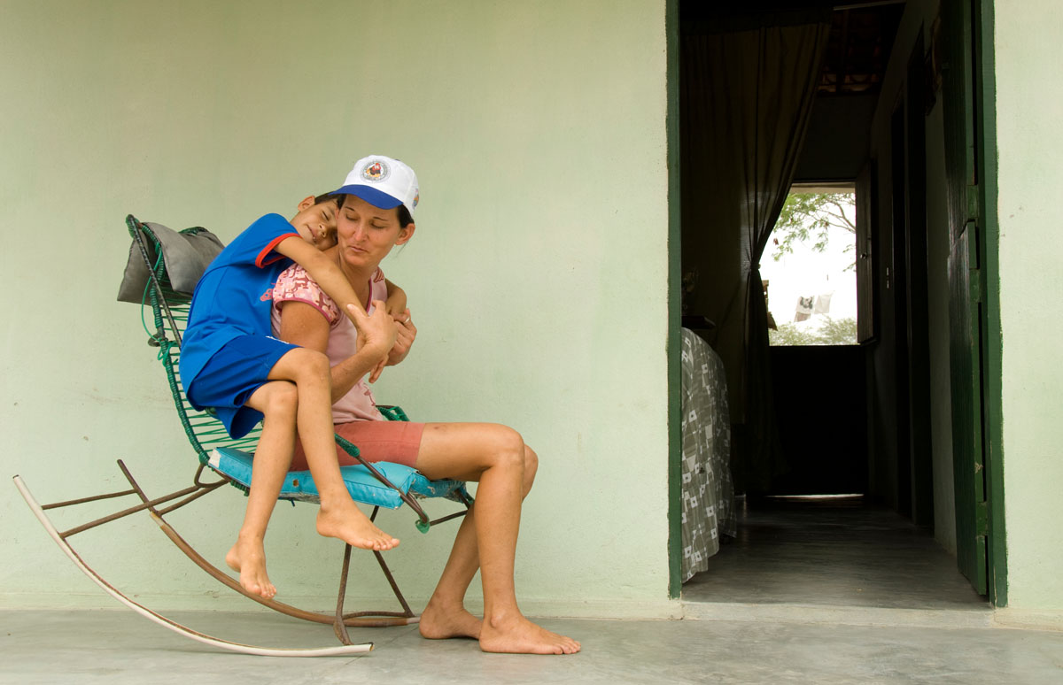 Valdenice de Oliveira sits on the porch of her Habitat home with her seven year-old son Vandeildo.  Before Habitat started building concrete houses here in 2006, most homes were made of dried mud, which not only required constant patching and reshaping but also served as a breeding ground for a type of beetle that poses a serious health threat to humans.© Habitat for Humanity International/Ezra Millstein