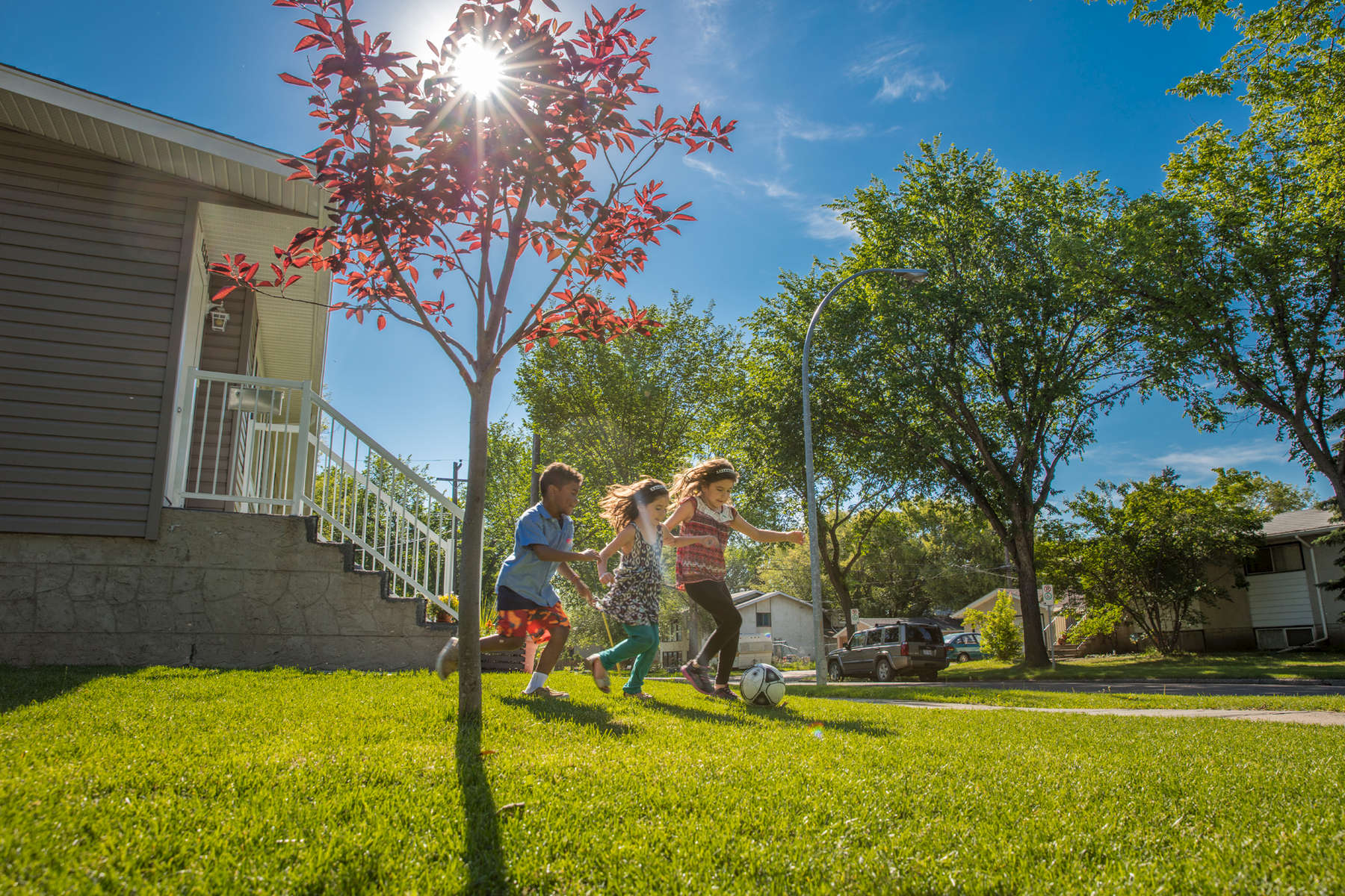 Siblings Ciera Nadeau (8, red shirt), Parnal Nadeau (6, blue shirt) and Ocean Nadeau (5, blue pants) play on the lawn in front of their family's Habitat home.© Habitat for Humanity International/Ezra Millstein