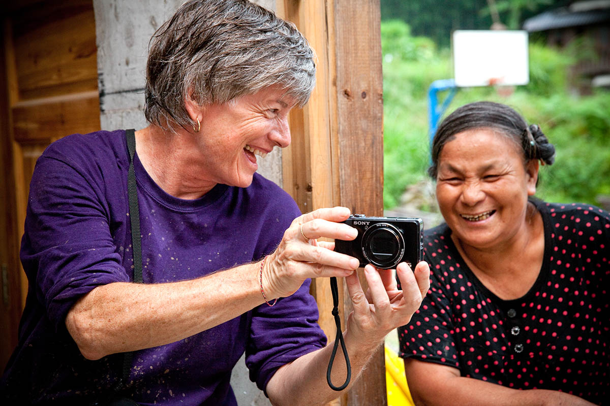 Global Village volunteer Linda McDowell (left), from Albuquerque, shares photos with a woman from Panrong village.  Linda spent a week helping to build new Habitat homes in the area.  Habitat for Humanity China offers microcredit loans to many families in the area who need to relocate due to dangerous landslides.©Habitat for Humanity International/Ezra Millstein