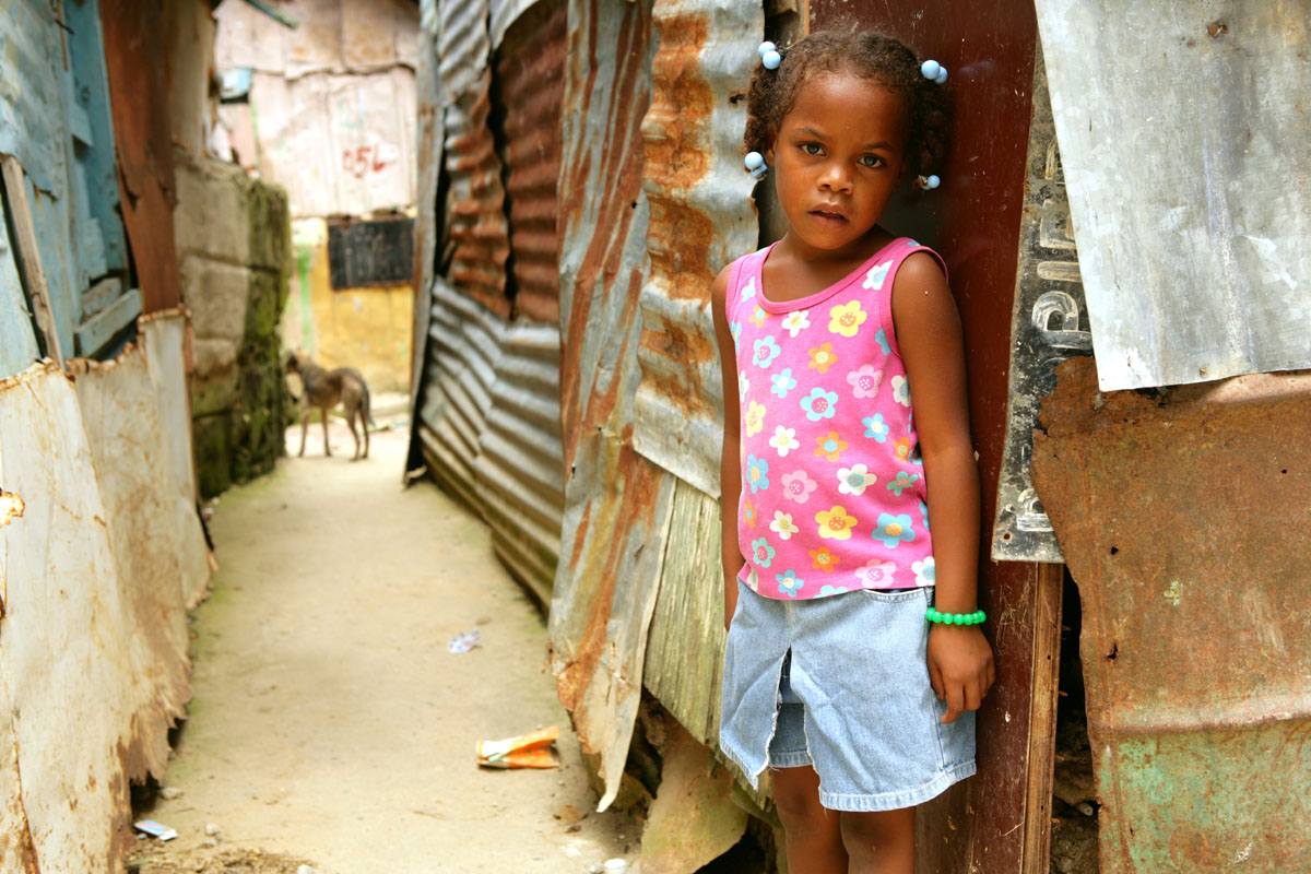 A young girl in front of her home in the La Lata neighborhood, on the banks of the Ozama River in Santo Domingo.  The area contains more than 200 squatter houses with as many as ten people in each house.  Homes are cobbled together with rusted pieces of metal, and have no plumbing.  Raw sewage runs through the streets, and the neighborhood frequently floods when the river rises.© Habitat for Humanity International/Ezra Millstein