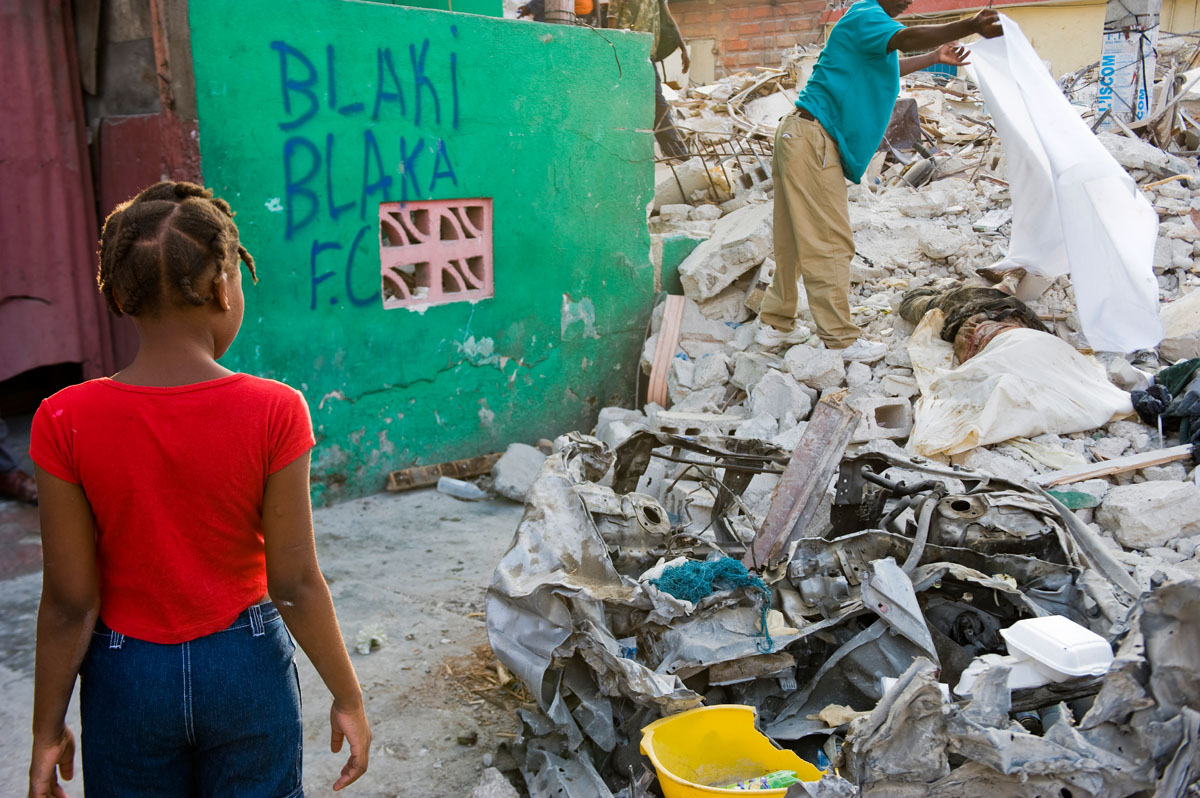 A young girl watches as a dead body is covered with a sheet, after being discovered decomposing in a pile of rubble three weeks after the January 12th earthquake. © Habitat for Humanity International/Ezra Millstein