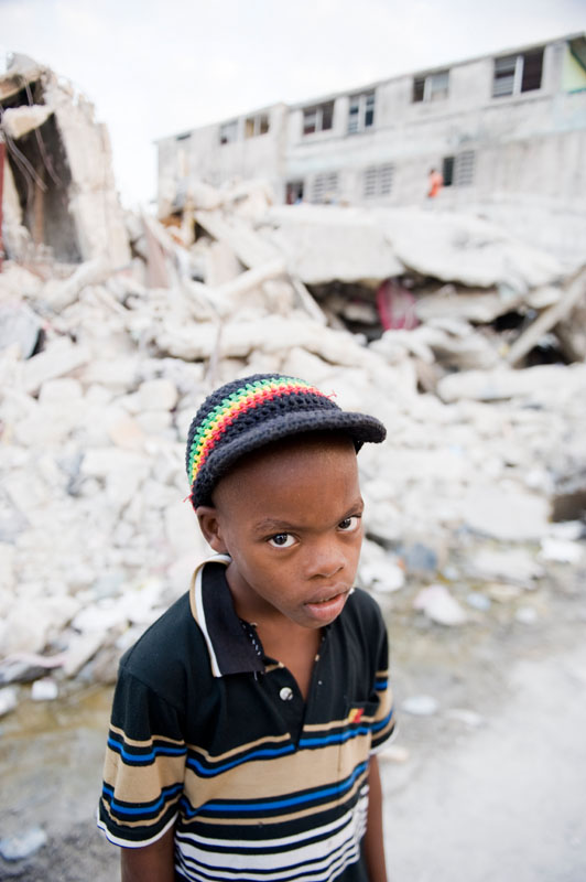 PORT-AU-PRINCE, HAITI (2/6/10)-Seven year-old Wesley Paul stands in front of a collapsed building in Port-au-Prince.   © Habitat for Humanity International/Ezra Millstein