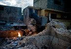 A man burns body parts among the ruins of a collapsed building, three weeks after the January 12th earthquake.  © Habitat for Humanity International/Ezra Millstein