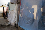 Five year-old Jonas Joseph, his eight year-old sister Marie and 12 year-old brother Jeff are silhouetted against the wall of their family's makeshift shelter, in the midst of a tent city that serves as a temporary home for 350 families.  The earthquake caused heavy damage to residential buildings in Carrefour; an estimated 80-90% of the buildings were destroyed.  © Habitat for Humanity International/Ezra Millstein