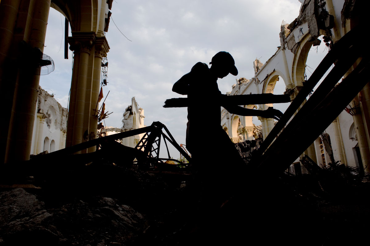 A man collects broken pieces of the pews in Haiti's National Cathedral, to use for firewood.  The building was destroyed by the January 12th earthquake.© Habitat for Humanity International/Ezra Millstein