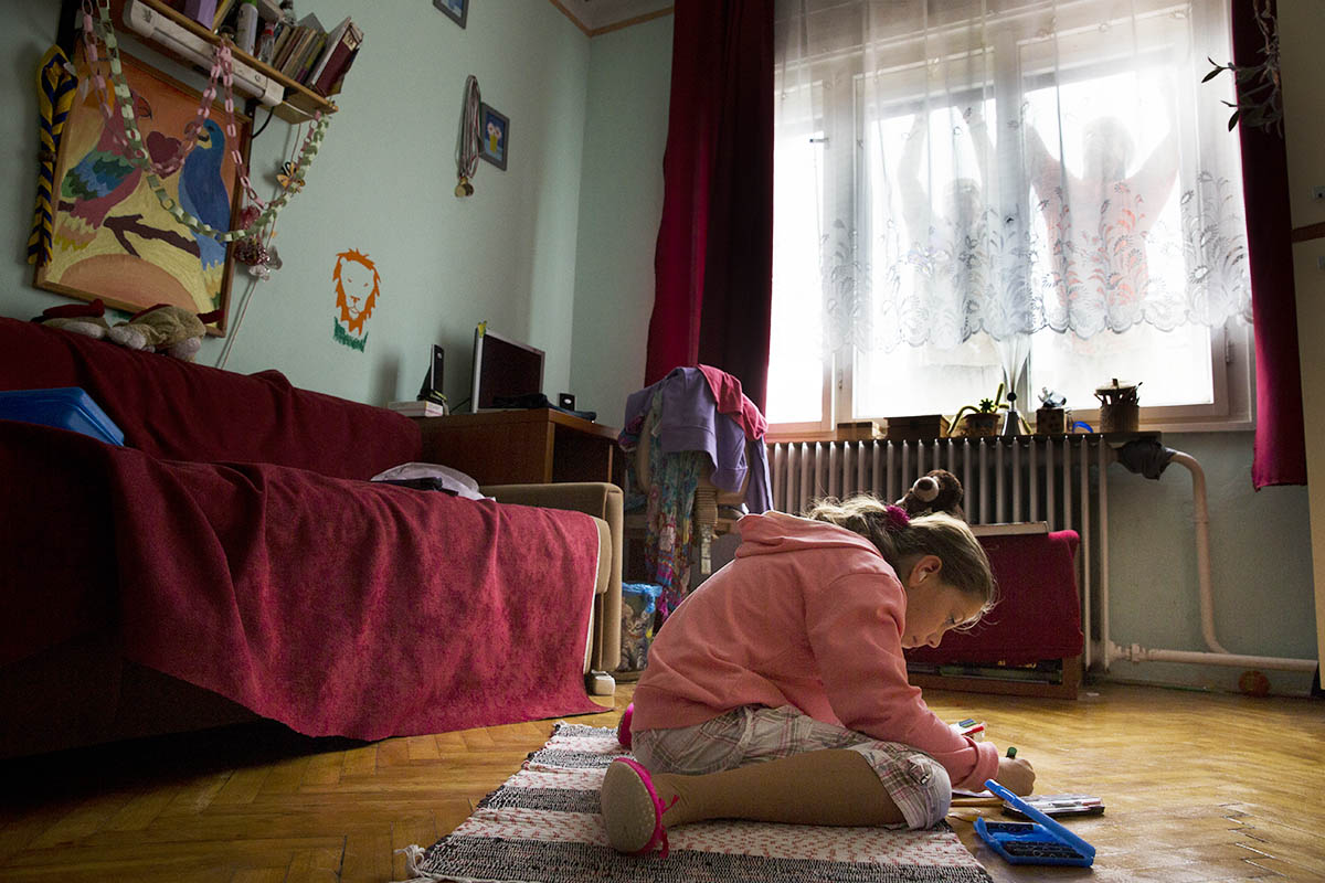 Anna Csapó (10) draws on the floor, while Habitat for Humanity volunteers attach insulating styrofoam to the outside of her family's home.  She lives in Vác  with her father Imre (47), mother Krisztina (45) and sister Sára (13).  Imre works as a caretaker at the local school, where Krisztina works as a janitor.  The family wanted to insulate their home for years, but their modest income made that impossible until they heard about HFH Hungary's thermal insulation program.  A Habitat Global Village team helped to insulate their home.©Habitat for Humanity International/Ezra Millstein