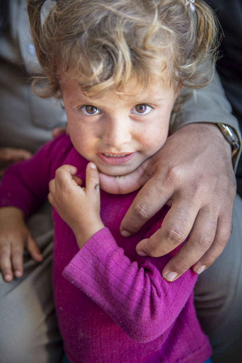 A girl, who did not want to give her name, waits for medical treatment at a mobile clinic, four miles from the Syrian border.  The refugees in the area are mostly from Hama, Syria, and they have poor access to health care. © Ezra Millstein