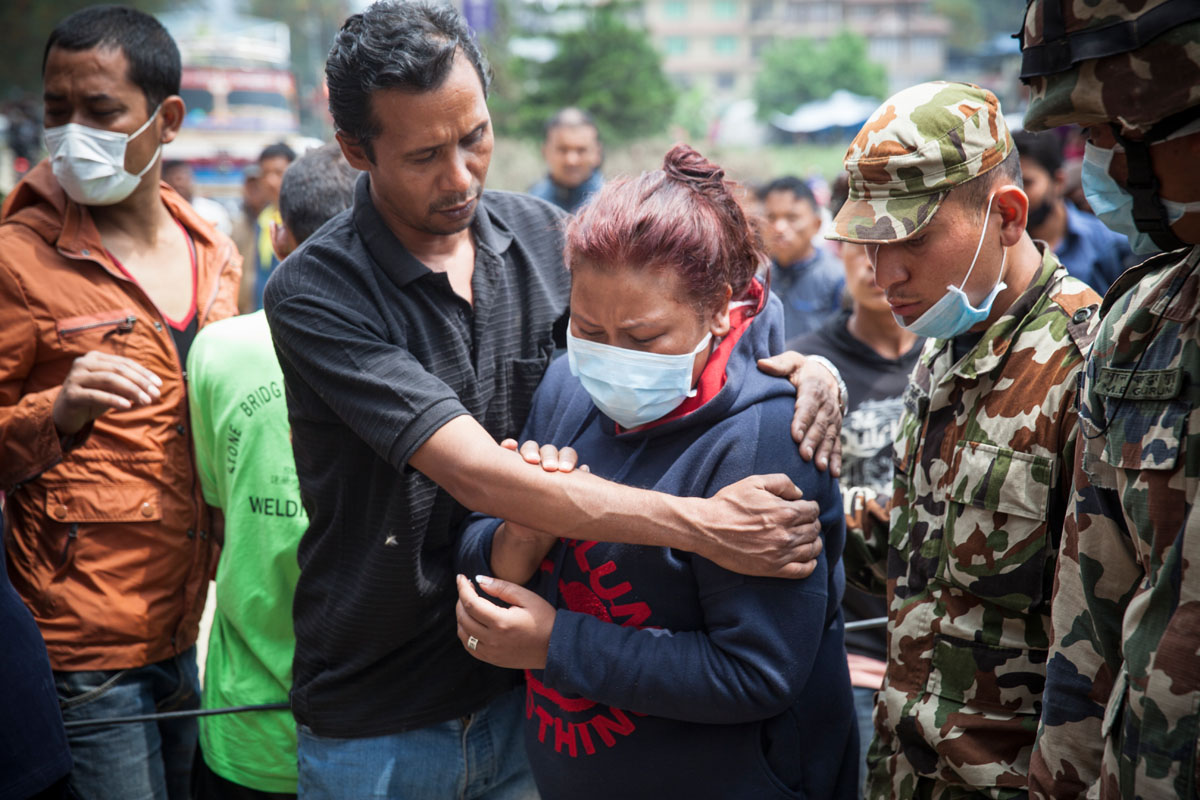 KATHMANDU, NEPAL (4/27/15)-A Nepali woman identifies the body of her dead cousin, after he was removed from a collapsed building, two days after a huge 7.8-magnitude earthquake struck Nepal, and was felt as far as India and Pakistan. © Habitat for Humanity International/Ezra Millstein