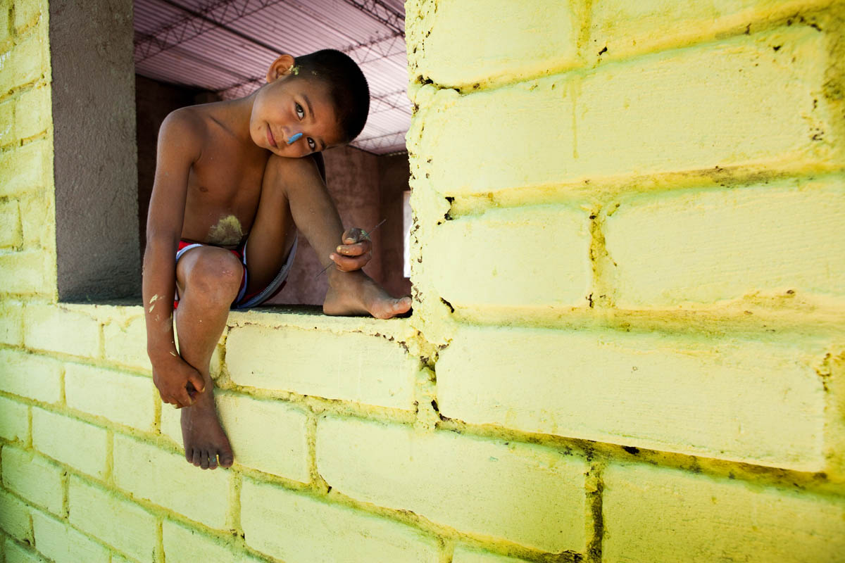 A boy watches as Habitat for Humanity volunteers help to paint his family's new Habitat home in the community of La Gallina.© Habitat for Humanity International/Ezra Millstein