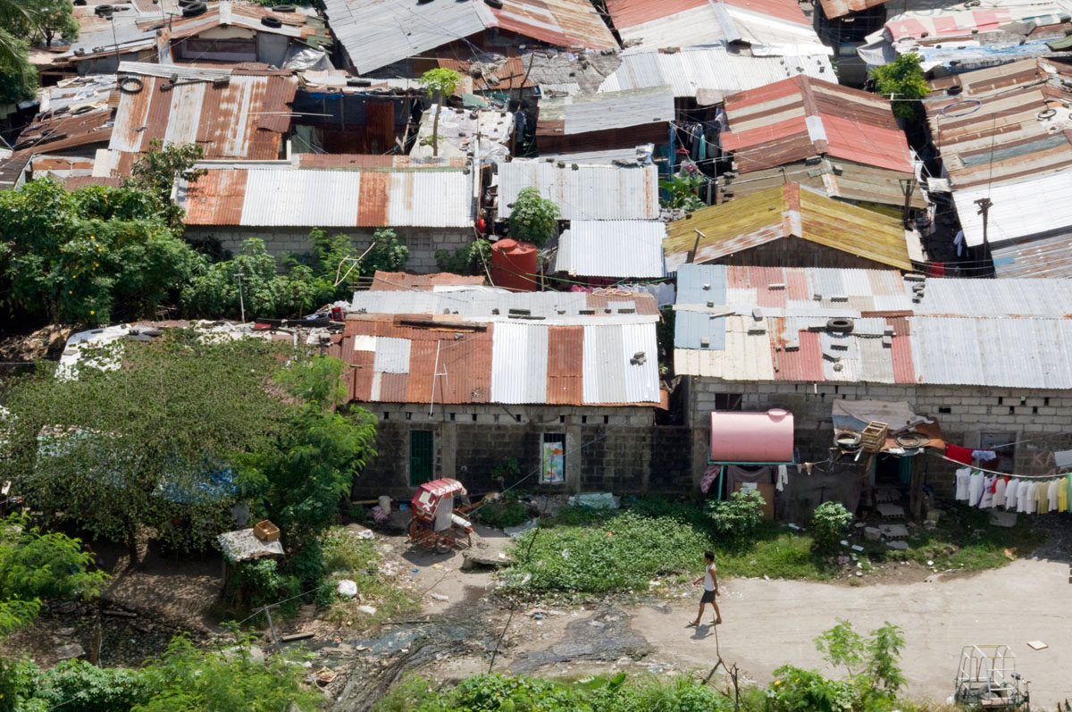 A man walks through the sprawling slums of the FTI neighborhood of Taguig City.  Families have relocated from this area to safe, durable and affordable three-story buildings constructed by Habitat for Humanity Philippines.  © Habitat for Humanity International/Ezra Millstein
