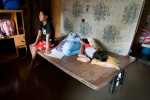 A mother sits beside her sleeping daughters in their flooded living room.  Typhoon Mirinae was the fourth storm to strike the country in a month, affecting an estimated 13,000 families.© Habitat for Humanity International/Ezra Millstein