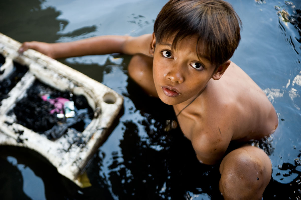 A young boy digs through sewage-filled water, searching for anything salvagable, on the Pasig River in the Paco Market neighborhood of Manila, one of the city's worst slums.  The neighborhood was hit particularly hard by the slew of typhoons.© Habitat for Humanity International/Ezra Millstein