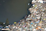 Brothers embrace as they stand on floating garbage on the Pasig River in the Paco Market neighborhood of Manila, one of the city's worst slums.  The neighborhood was hit particularly hard by the slew of typhoons.© Habitat for Humanity International/Ezra Millstein